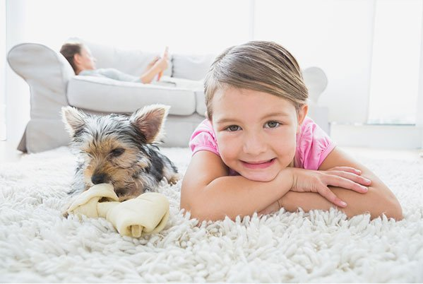 girl and dog laying on clean carpet in van buren ar